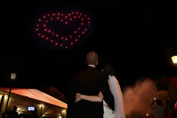 Happy hugging bride and groom watching beautiful colorful fireworks night sky